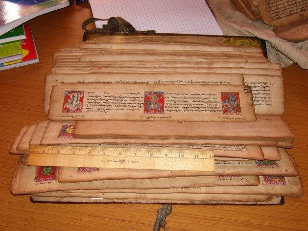 Pechas, or traditional Tibetan books, consist of loose leaves of handmade paper wrapped in cloth, placed between wooden boards, and secured with a belt.