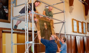 Workers re-hang portraits of historic Duke luminaries in the renovated Gothic Reading Room, July 2015.