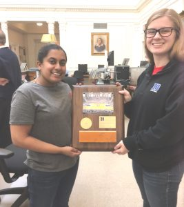 Two women students holding plaque