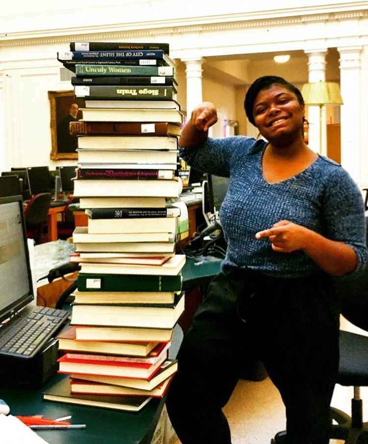 Tall stack of books on desk with woman